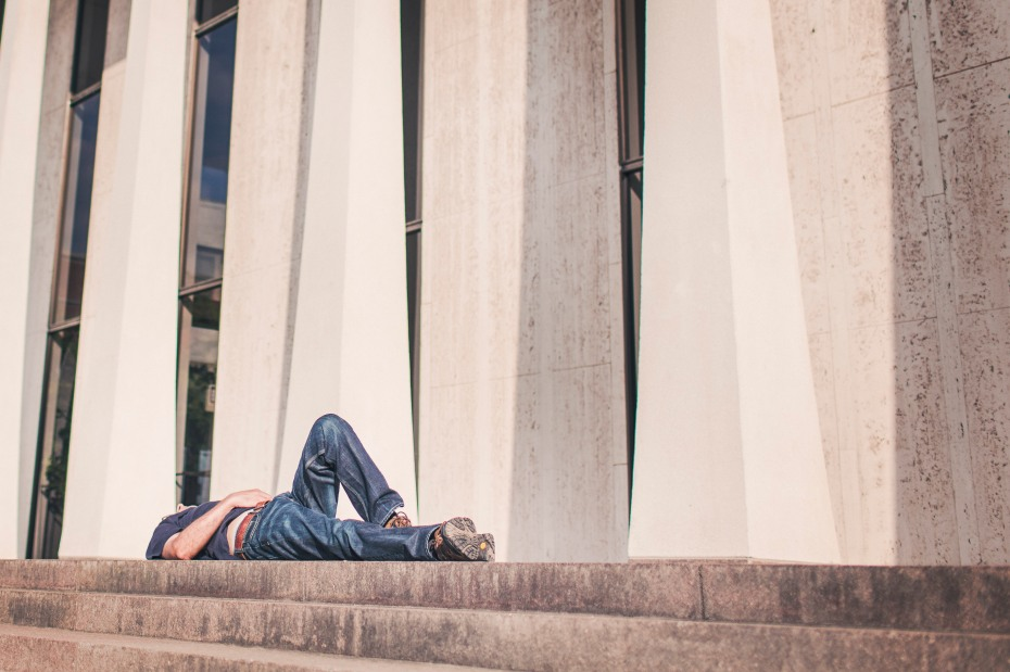 Guy laying on his back in front of building.